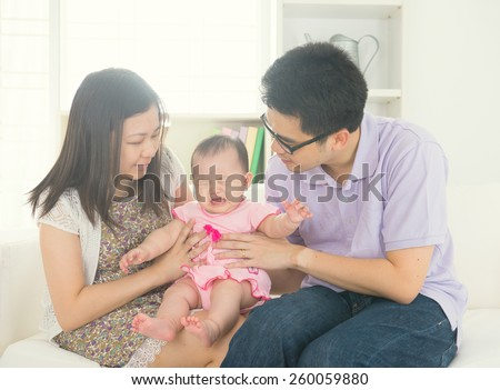 asian parent with crying baby - stock photo