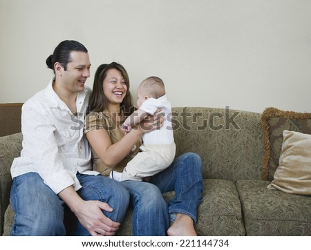 Asian parents smiling at baby - stock photo