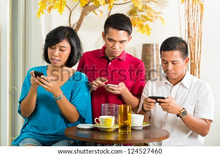 Asian people having fun together with mobile phone and drinking coffee or cocktail - stock photo