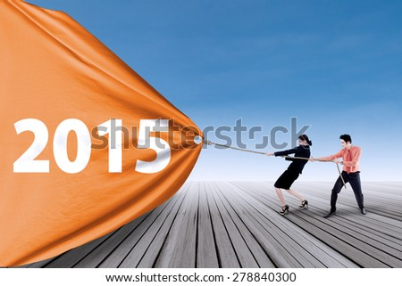 Asian people take over a banner new year 2015 outdoors - stock photo