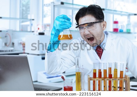 Asian person working in laboratory and doing experiment with chemical fluid - stock photo