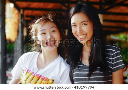 asian playful younger sister and older sister smiling happily