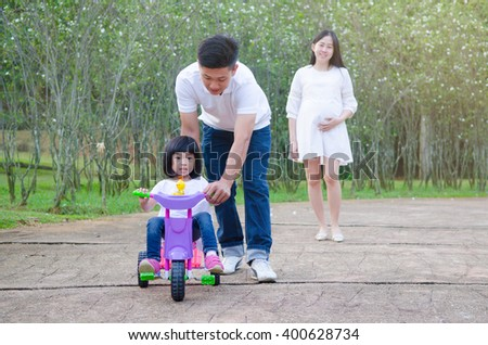 Asian playing with their daughter in the garden - stock photo