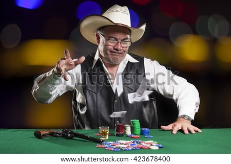 Asian Poker Player wearing cowboy hat. Cowboy is throwing cards, folding, and has a glass of whiskey and a gun on the gaming table. Background is dark with blurred lights. - stock photo