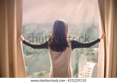 Asian portrait beautiful woman opening curtains and building cityscape background - stock photo