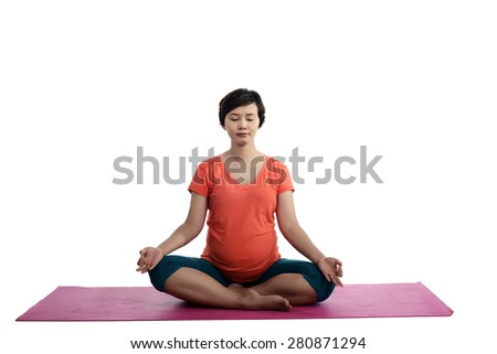 Asian pregnant woman doing yoga over isolated white background - stock photo