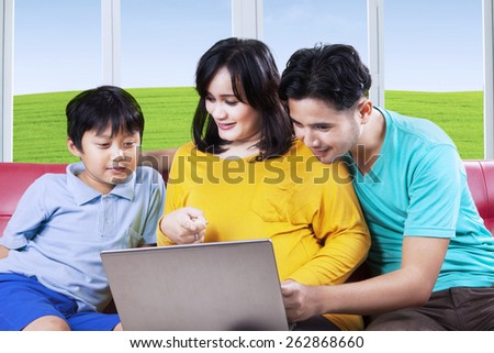 Asian pregnant woman with son and husband using laptop computer at home - stock photo