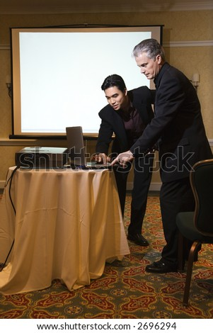 Asian prime adult businessman helping prime adult Caucasian businessman give presentation.