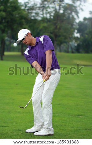 Asian professional golfer chipping