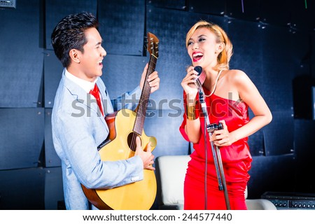 Asian professional singer and guitarist recording new song or album CD in studio - stock photo