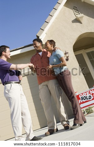 Asian real estate agent with African American couple buying new house - stock photo