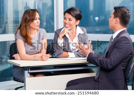 Asian recruitment team hiring candidate in job interview - stock photo