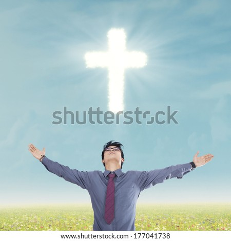 Asian religious man with arms wide open standing below a glowing cross - stock photo