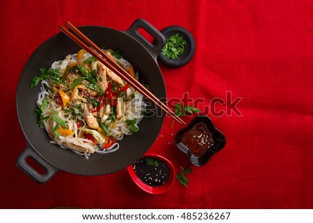 Asian rice noodles wok with chicken and vegetables, selective focus. top view of a horizontal