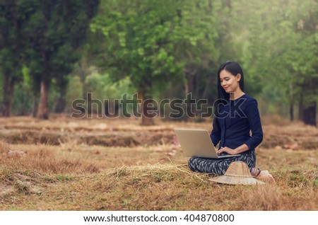 Asian rural woman using computer on the Straw at the countryside, Countryside business concept - stock photo