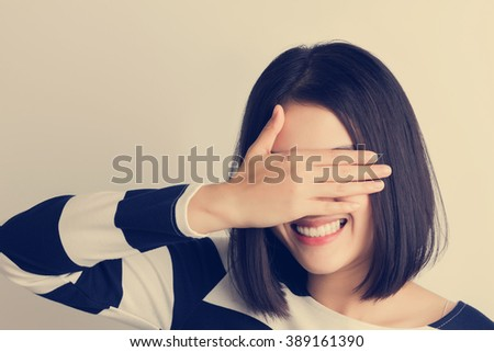 Asian 20s girl smiling in playing hide-and-seek for joy and serenity,vintage tone filter. - stock photo