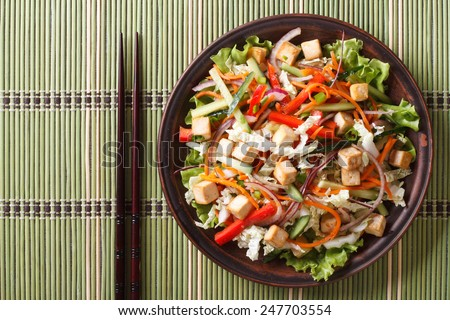 Asian salad with tofu and fresh vegetables close up on a plate. horizontal view from above  - stock photo