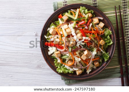 Asian salad with tofu and vegetables close-up on the table. horizontal view from above  - stock photo