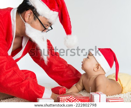 Asian santa claus with baby boy, many Christmas presents on floor. - stock photo