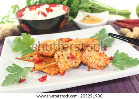 Asian satay skewers with peanut sauce and rice on a light background