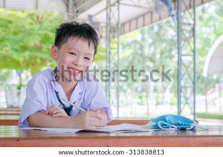 Asian schoolboy in uniform doing homework at school