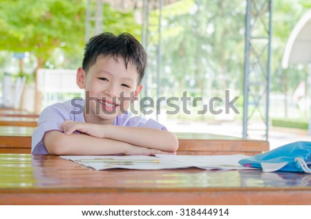 Asian schoolboy in uniform doing homework at school - stock photo