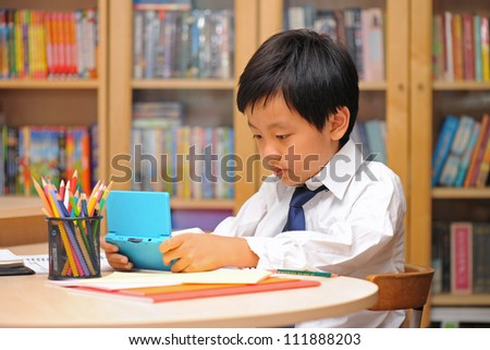Asian schoolboy in white shirt distracted by portable game machine during homework time