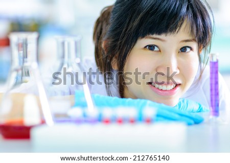 Asian scienctist woman looking pensively at tubing with solutions - stock photo