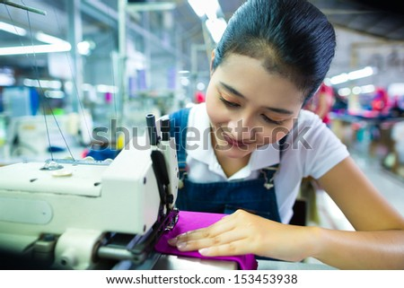 Asian Seamstress or worker in a Indonesian factory sewing with a industrial sewing machine, she is very accurate - stock photo
