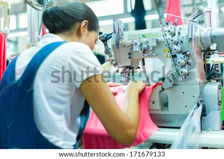 Asian Seamstress or worker in an Asian textile factory sewing with a industrial sewing machine, she is very accurate