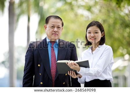Asian senior businessman & young female executive walking