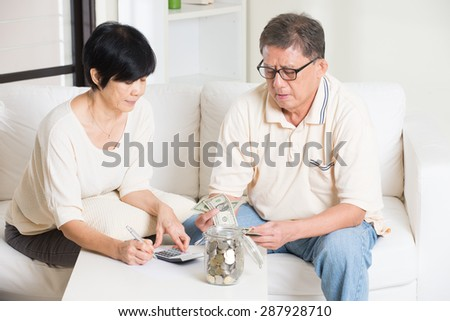 asian senior couple calculating finance at their home  - stock photo