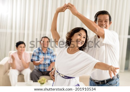 Asian senior couple dancing while their friends are cheering in background - stock photo