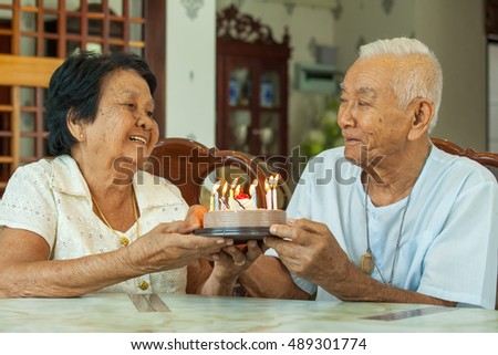 Asian senior couple holding a cake and smiling in living room