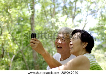 Asian senior couple using cell phone in nature, happiness when get connected with their children concept - stock photo