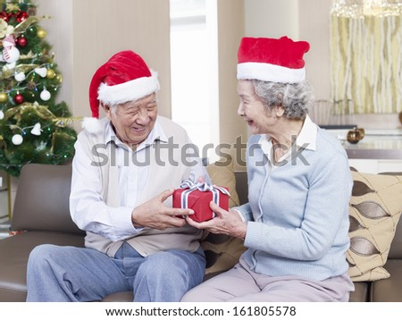 Asian senior couple with Christmas hats exchanging gifts. - stock photo