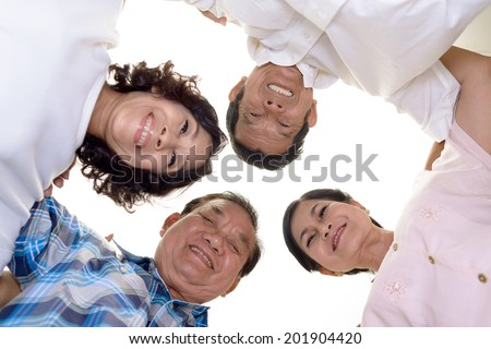 Asian senior friends standing in a huddle and looking at the camera, view from below - stock photo