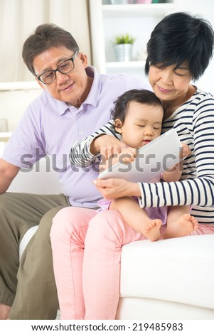asian senior grand parents teaching grand son with tablet