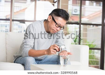 asian senior male taking pills in despair - stock photo