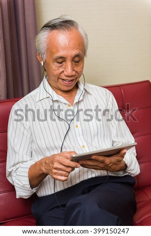 Asian senior male using technology for entertainment. Lifelong learning concepts.