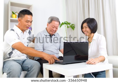 Asian senior man learns to use tablet computer - stock photo