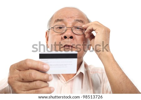 Asian senior man looking at credit card on white background