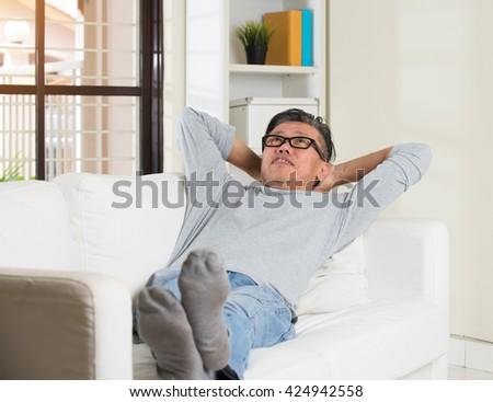 asian senior man relaxing on sofa at home - stock photo