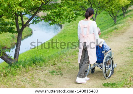 Asian senior man sitting on a wheelchair with caregiver - stock photo