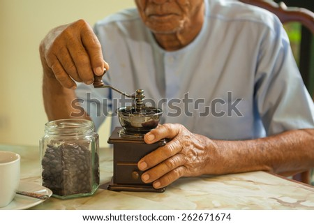 Asian senior man with vintage coffee grinder and coffee beans - stock photo