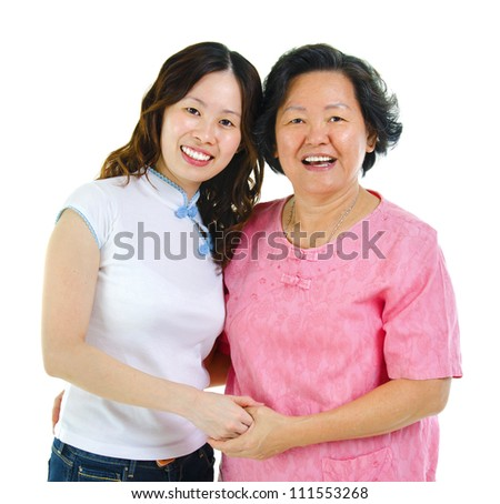 Asian senior mother and daughter holding hands over white background - stock photo