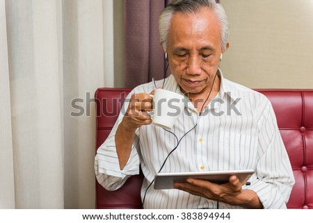 Asian senior relaxing with drink and entertainment on tablet.