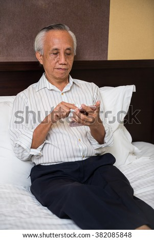 Asian senior sitting on bed learning new technology.