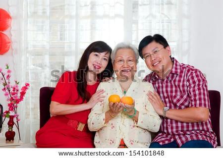 Asian senior woman and children celebrating chinese new year - stock photo