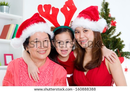 Asian senior woman and daughter and granddaughter celebrate christmas - stock photo